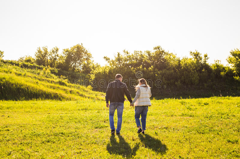 Couple walking in autumn sunset countryside meadow holding hands royalty free stock photo