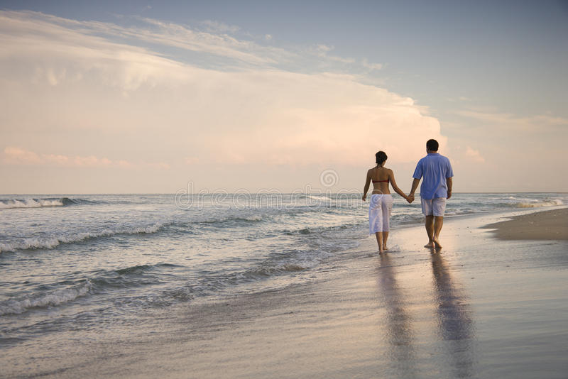 Couple Walking on Beach. Rear view of a couple walking on the beach, holding hands. Horizontal shot stock images