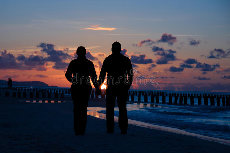 Couple walking on beach royalty free stock images