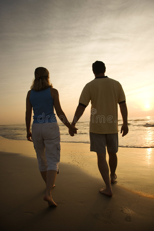 Couple walking on beach. Caucasian mid-adult couple walking holding hands on beach at sunset stock images