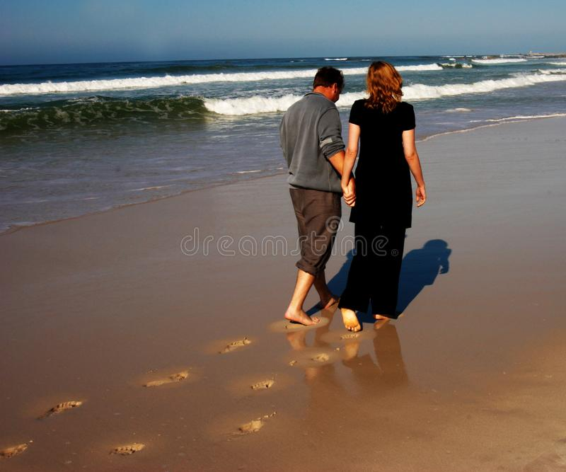 Couple walking on the beach royalty free stock photography