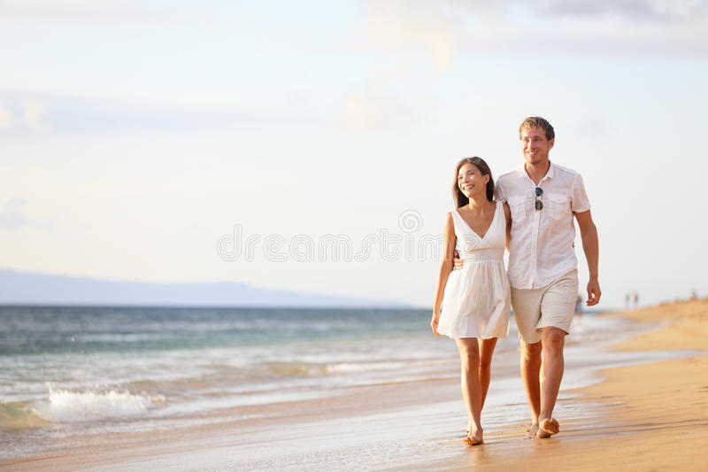 Couple walking on beach. Young happy interracial  smiling holding around each other. Asian woman, Caucasian man