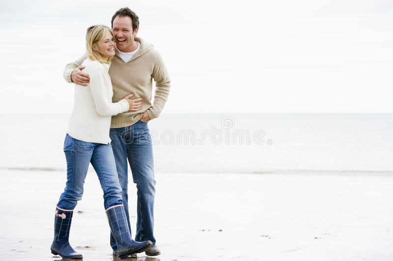 Couple walking on beach arm in arm smiling stock photo