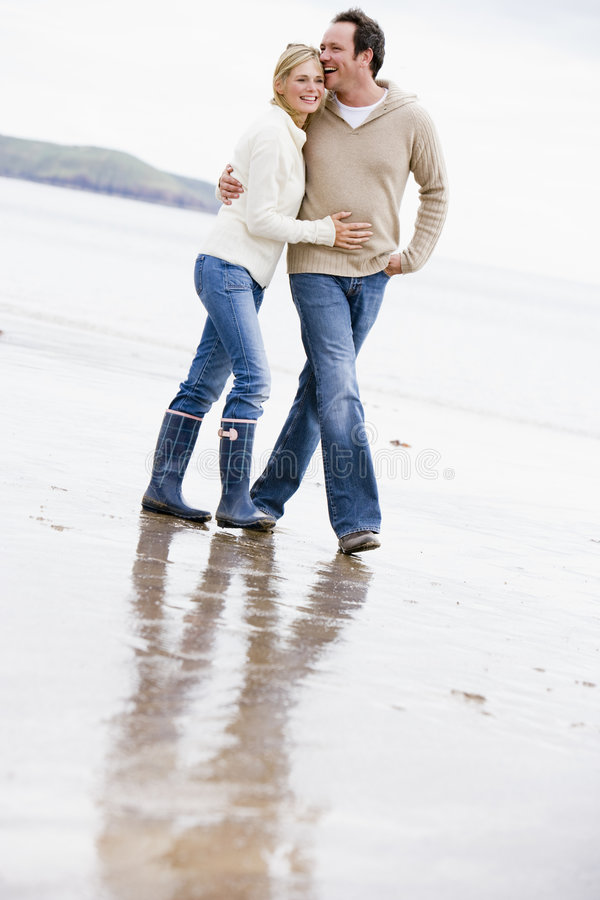 Couple walking on beach arm in arm smiling royalty free stock photo