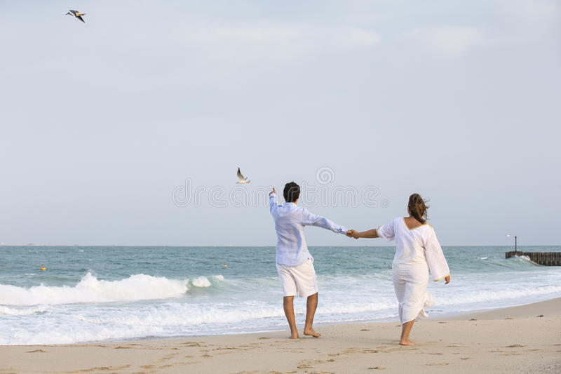 Couple walking on the beach royalty free stock photo