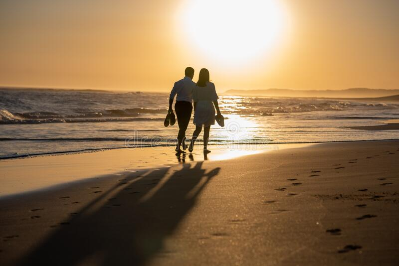 Couple walking on the beach during golden hour stock images