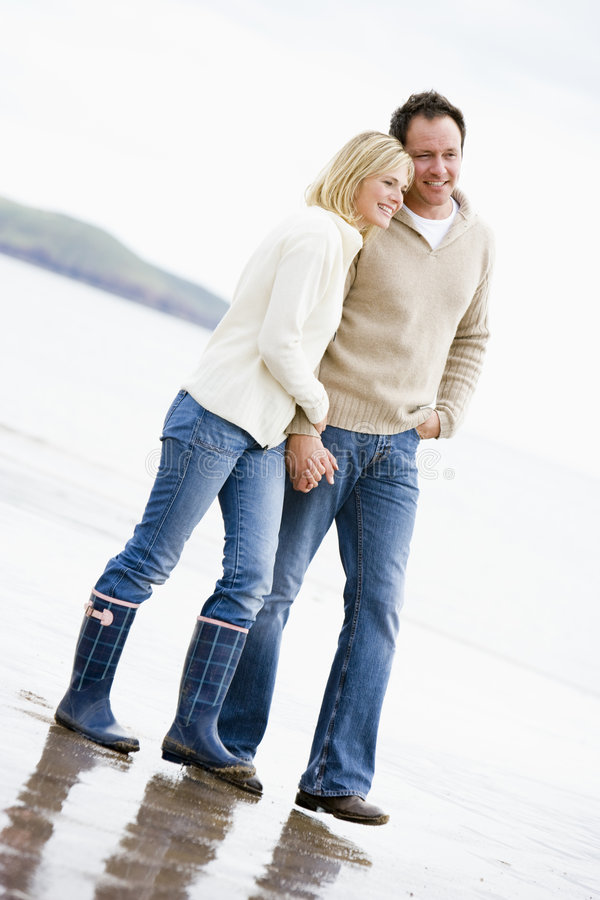 Couple walking on beach holding hands smiling royalty free stock image