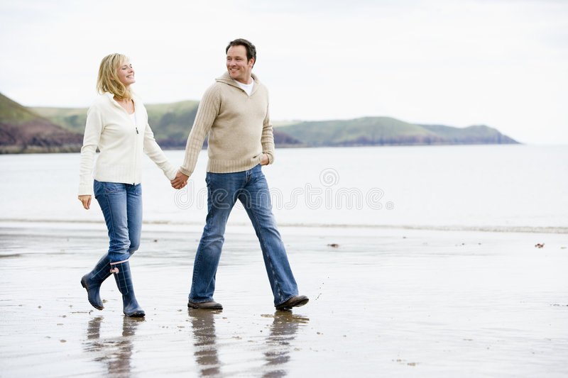 Couple walking on beach holding hands smiling royalty free stock photography