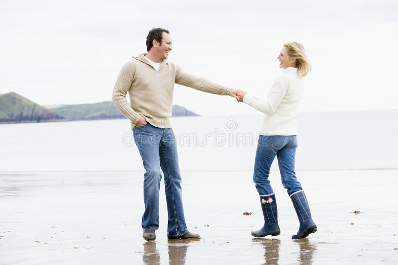 Couple walking on beach holding hands smiling royalty free stock photo