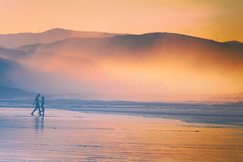Couple walking on beach at sunset. Couple walking on beach at the sunset stock photo