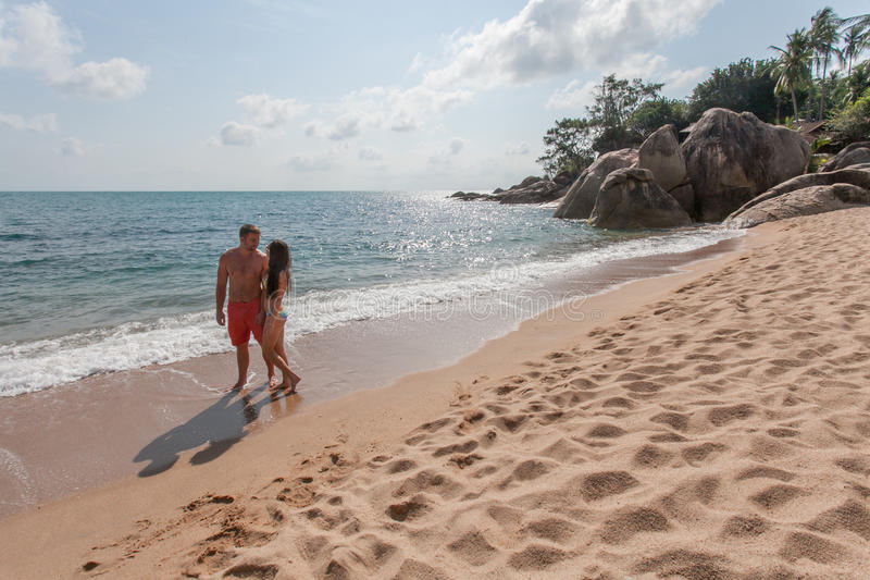 Couple walking on beach. Young happy couple walking on beach smiling holding around each other. royalty free stock images