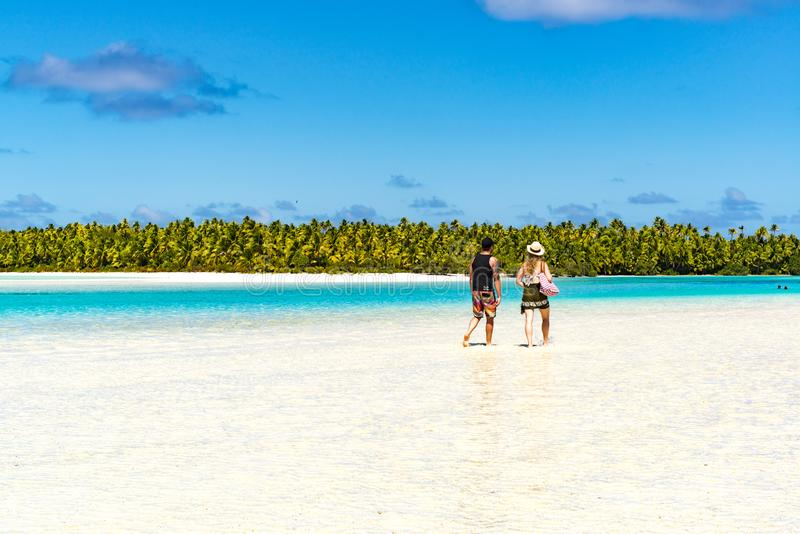 People walking through clear water over white sand South Pacific Island royalty free stock photography