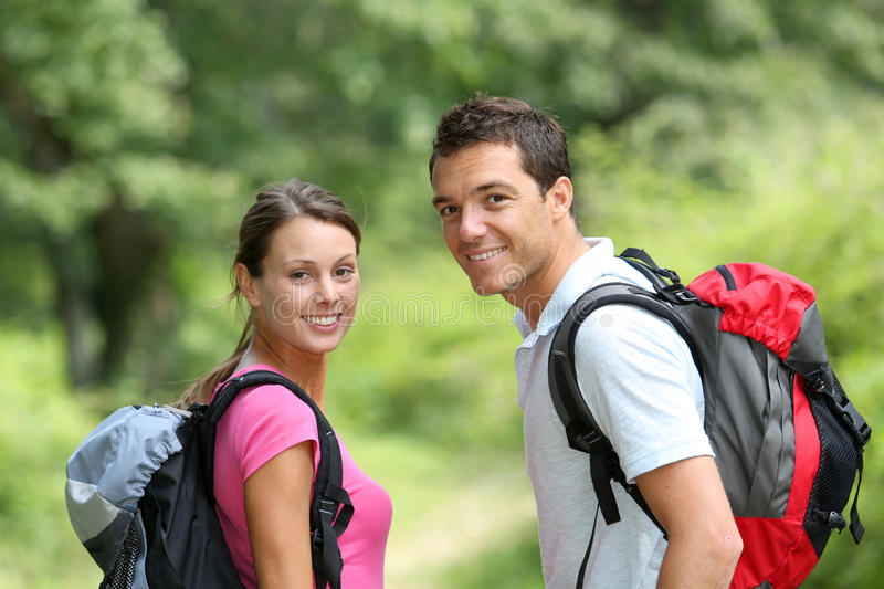 Couple walking in countryside. Portrait of happy couple on a trekking day stock photo