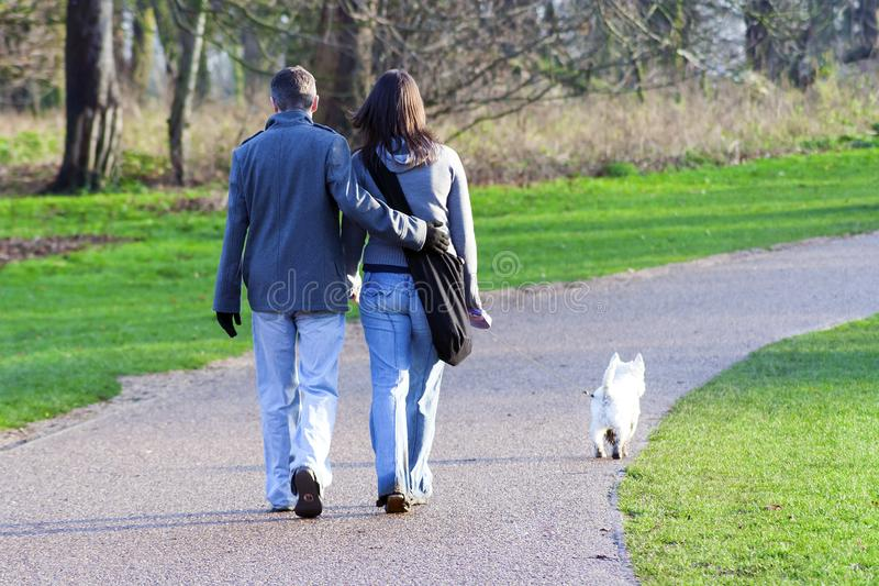 Couple Walking Dog in the Countryside royalty free stock photography