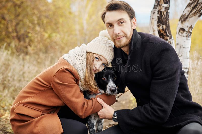 Couple walking with dog in the Park and hugging. Autumn walk men stock photos