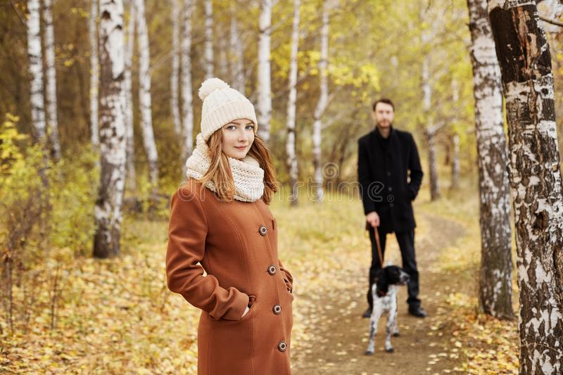 Couple walking with dog in the Park and hugging. Autumn walk men royalty free stock image