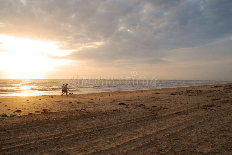 Download Couple Walking The Dog At Sunrise Stock Photo - Image: 4459872