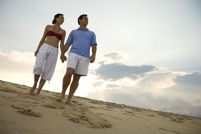 Couple walking down beach. Caucasian mid-adult couple holding hands walking on beach royalty free stock photos