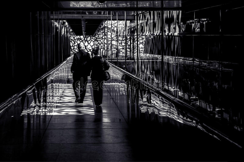 Couple walking down contrasted corridor. Old couple walking down a contrasted corridor stock photos