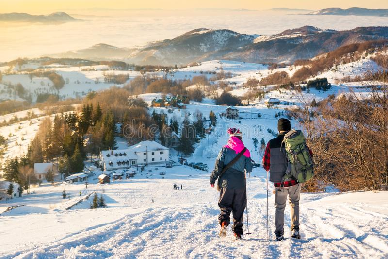 Couple walking down the snowy mountain in sunset time royalty free stock photos