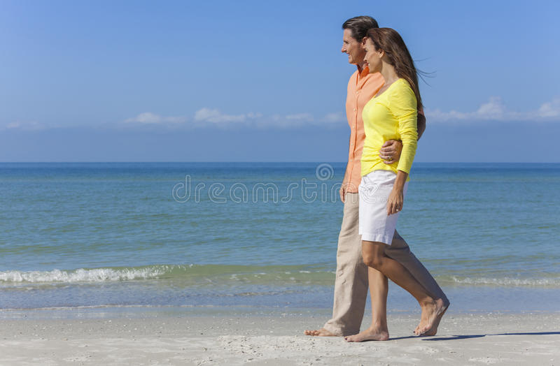 Couple Walking on An Empty Beach royalty free stock image