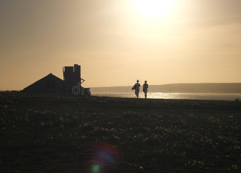 Couple walking in the hill with. Sunset hour royalty free stock photos