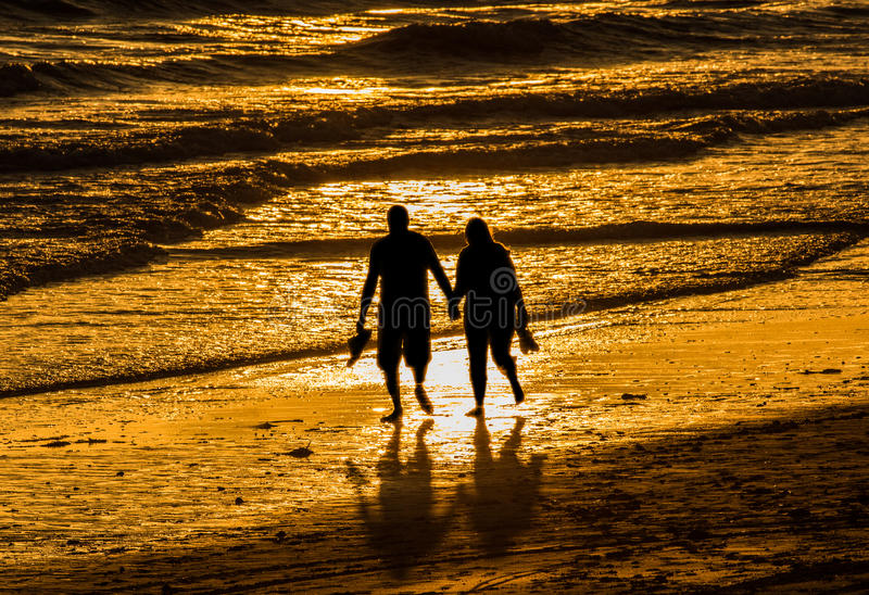 Couple walking holding hands beach. Silhouette couple walking at sunset on the beach holding hands. Love, romance, valentines concept royalty free stock photography