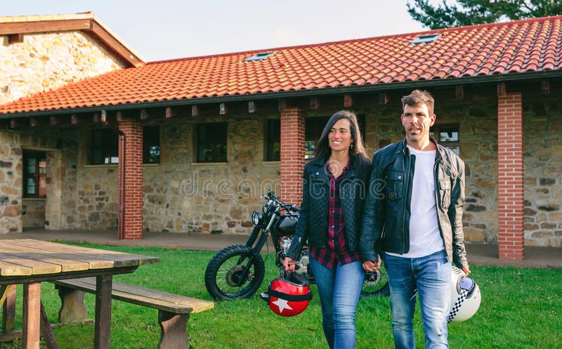 Couple walking holding hands and custom motorcycle. Young couple walking holding hands outdoors with custom motorcycle in the background royalty free stock photography