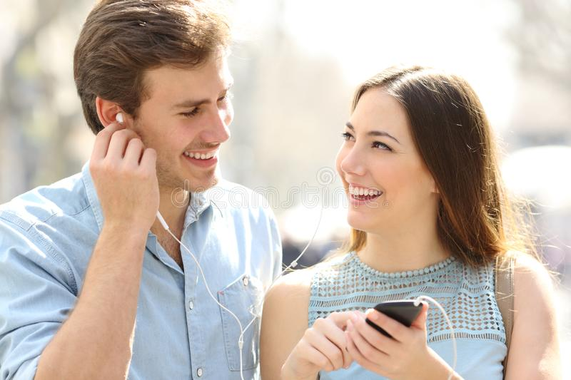 Couple walking listening to music sharing earphones stock image