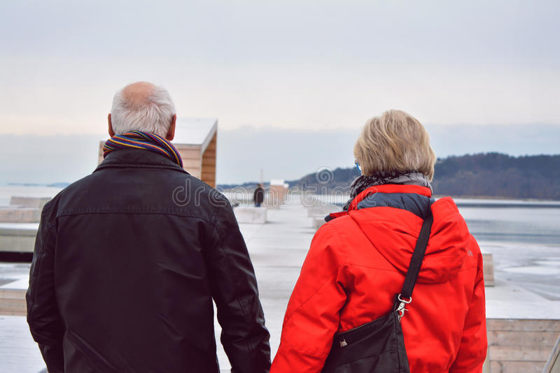 Couple walking on a long pier, on a cold winter day. Focus on senior couple holding hands walking on a long pier, a cold winter afternoon royalty free stock photography