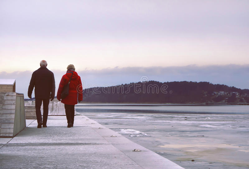 Couple walking on a long pier, by sunset on a beautiful winter day. stock photos