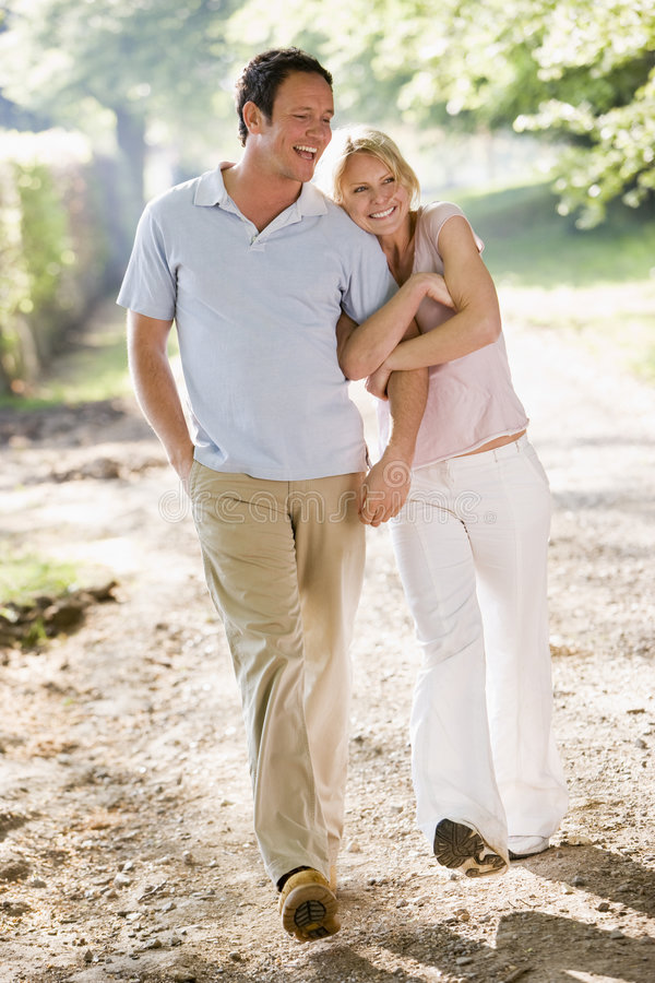 Couple walking outdoors arm in arm smiling stock photography