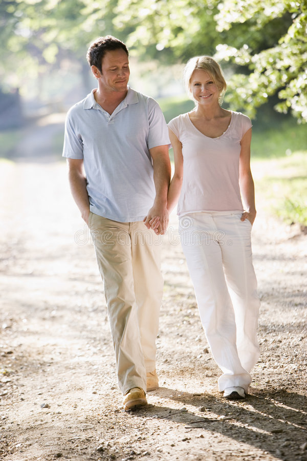 Couple walking outdoors holding hands and smiling stock photo