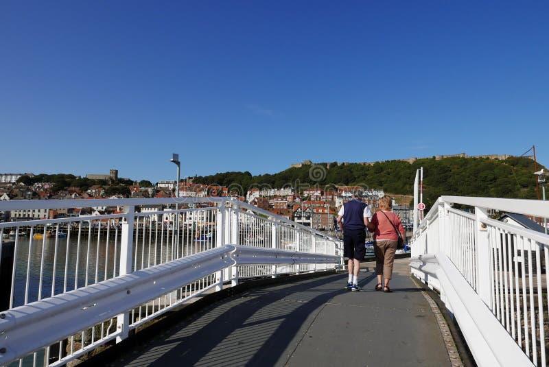 Couple walking over bridge stock image