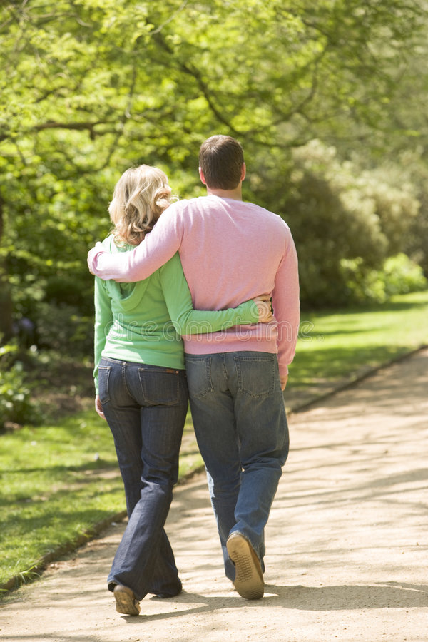 Couple walking on path arm in arm