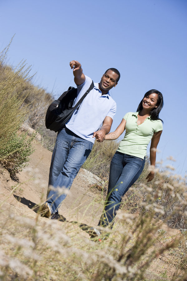 Couple walking on path holding hands and smiling stock images