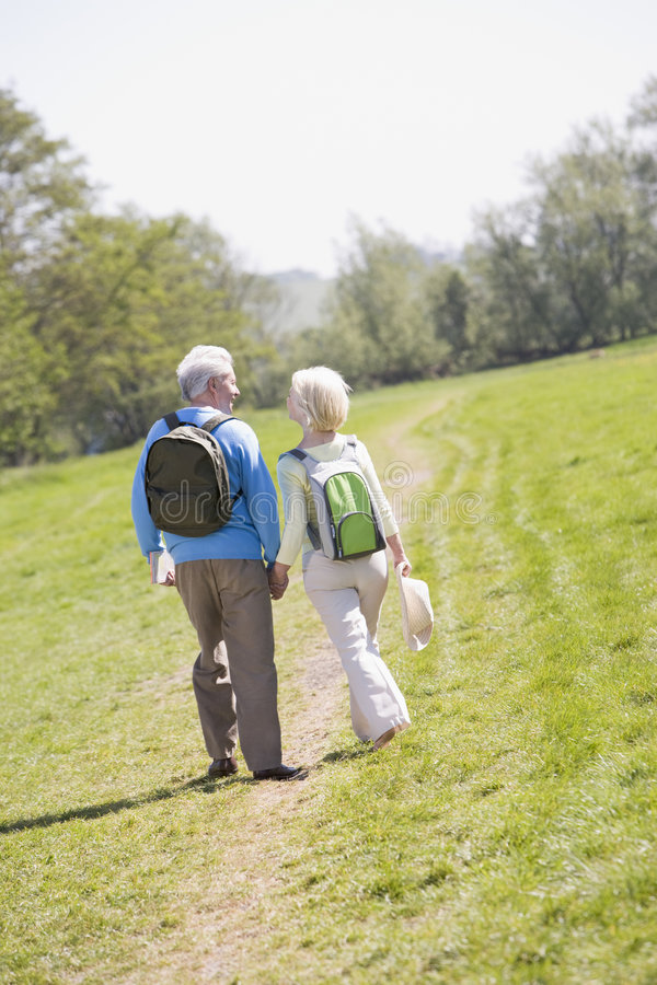 Download Couple Walking On Path In Park Holding Hands Stock Photos - Image: 5559993
