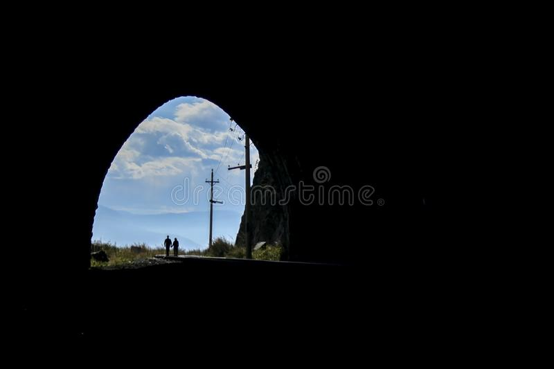 Couple walking on the railroad view from the tunnel. Black background and bright exit from the tunnel with a blue sky royalty free stock images