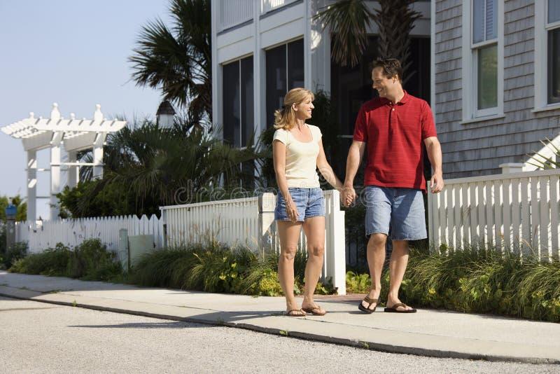 Couple walking on sidewalk.