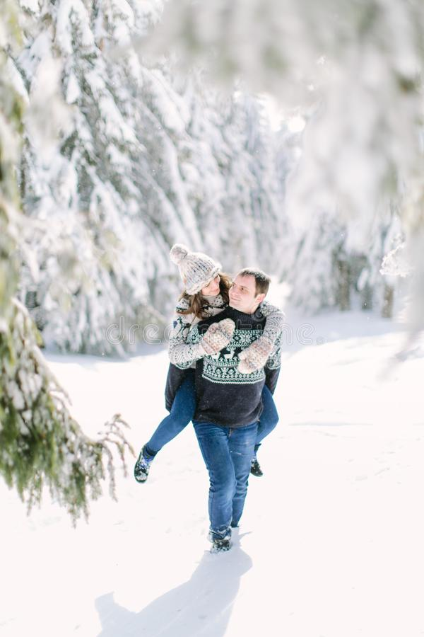 Couple walking in snowy field piggyback.  royalty free stock photo
