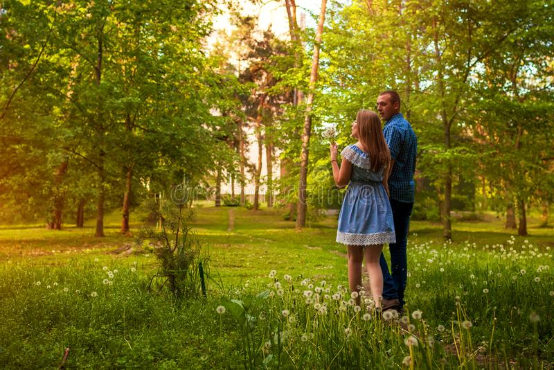 Couple walking in spring forest. Young man and woman blowing dandelions at sunset. royalty free stock photo
