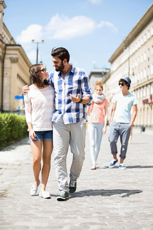 Couple walking on street with friends in background stock photos