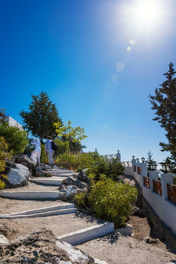 Couple walking up white painted stairs to Tsambika Monastery, R royalty free stock image