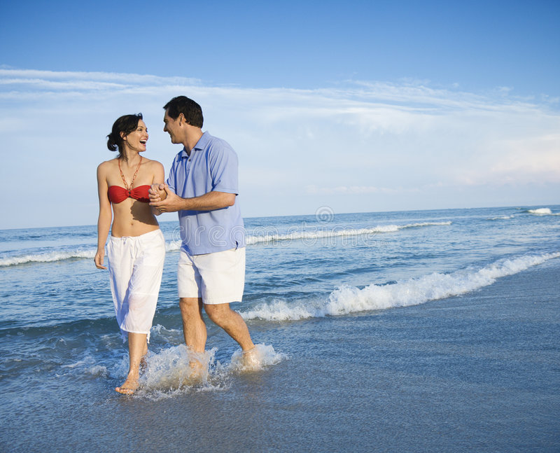 Couple walking in waves. Caucasian mid-adult couple holding hands wading in ocean stock photography