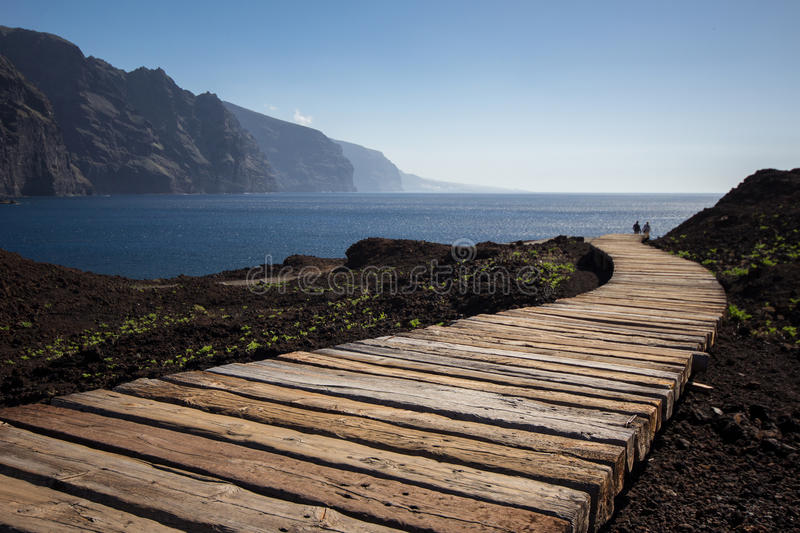 Couple walking on wooden path to ocean royalty free stock photo