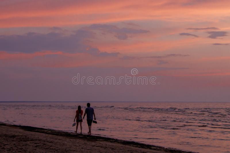 Couple walks barefoot along sea coast during colorful sunset. Jurmala beach, Baltic seaside, Latvia. royalty free stock image