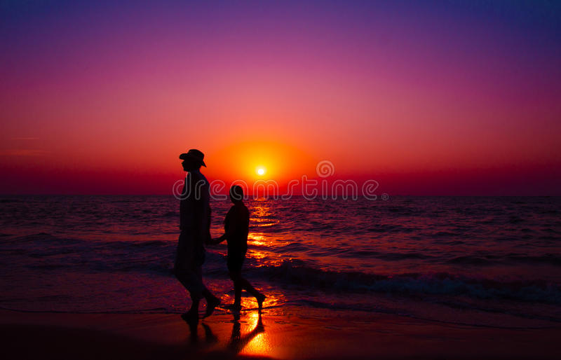 Couple walks on the beach with a sunset - Stock Image stock images