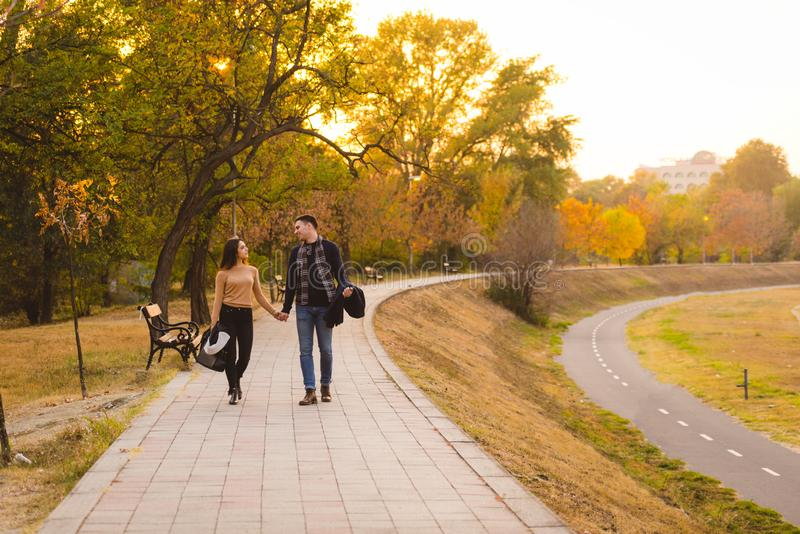Couple walks in the park at sunset feeling loved stock image