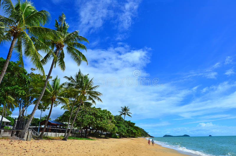 Couple walks on Trinity beach near Cairns Queensland Australia royalty free stock photography