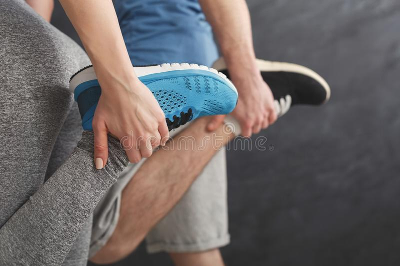 Couple warming up legs before training stock images